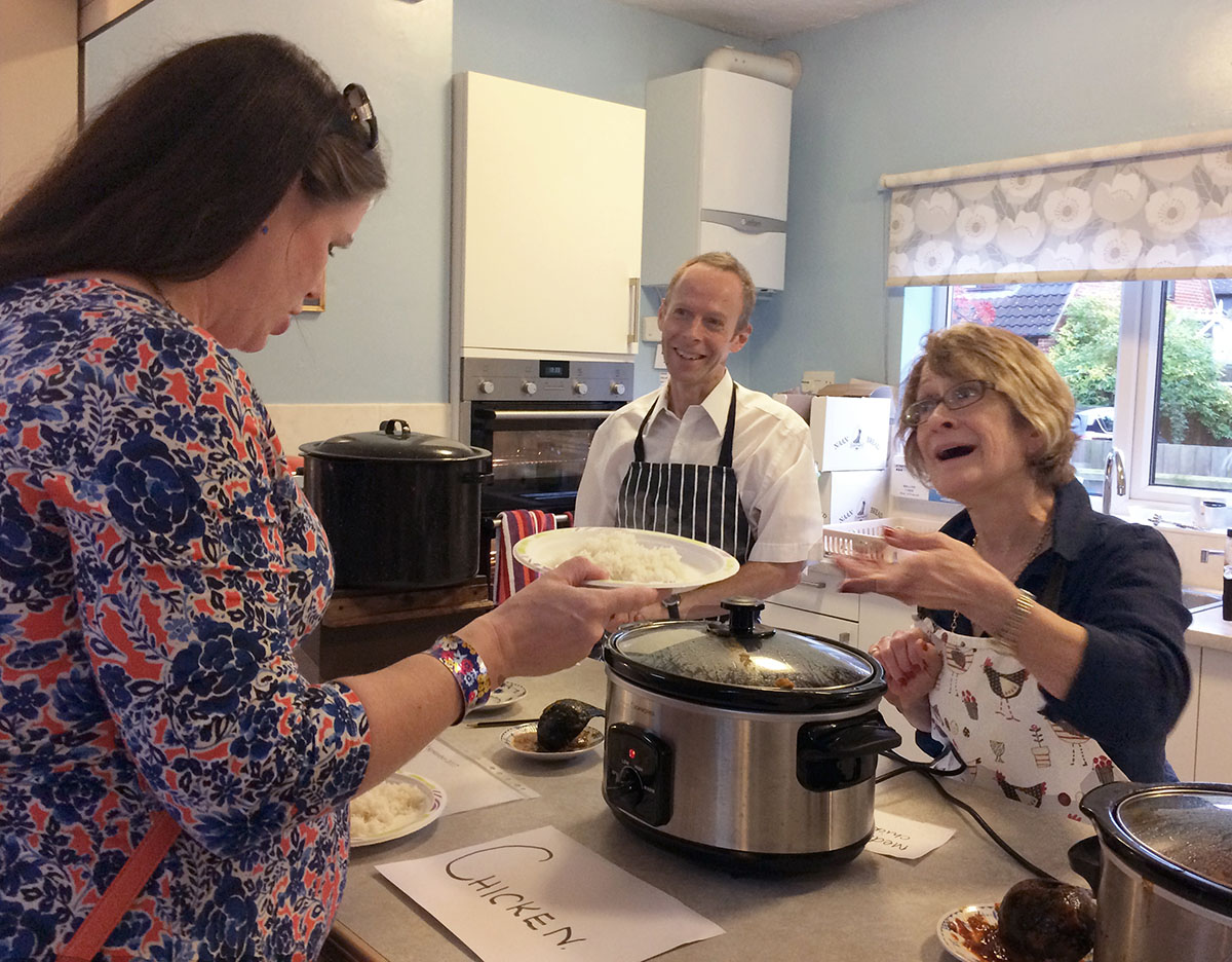 Villagers offer a choice of curries through the kitchen serving hatch as part of a fundraiser.