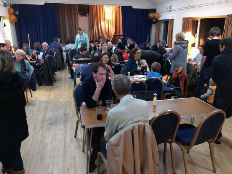 Villagers gather around tables to enjoy curry and beer as part of a fundraiser.