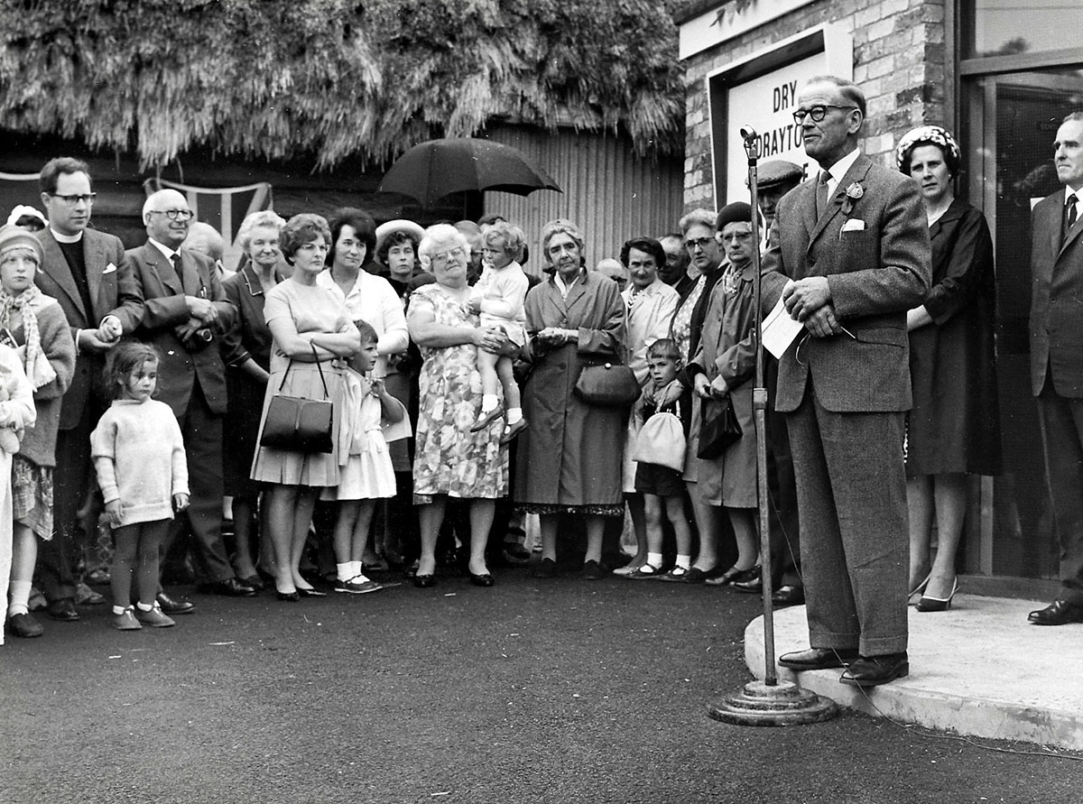 A man speaks into a microphone on the front step of the village hall. Villagers form a circle around him to listen.